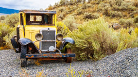 Abandoned old Car in a Field. Abandoned and damaged vintage Yellow Car in a Field in the semi desert area of central British Columbia Royalty Free Stock Images