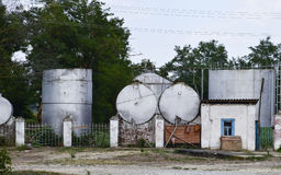Almost abandoned old gas station for agricultural machinery. Barrels of combustible fuel Stock Photo