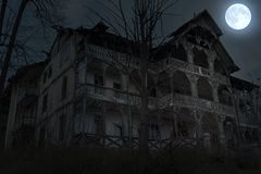 Abandoned old haunted house with dark horror atmosphere in the moonlight royalty free stock photo