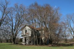Abandoned old house in rural Indiana. Abandoned old wooden two story house in rural countryside with trees surrounding it Stock Photography