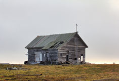 Abandoned old hunting house in tundra of Novaya Zemlya archipelago. Wooden hunting Lodge in open tundra, partially destroyed by hurricane royalty free stock photos