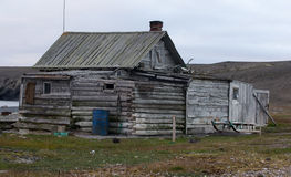 Abandoned old hunting house in tundra of Novaya Zemlya archipelago. Wooden hunting Lodge in open tundra, partially destroyed by hurricane royalty free stock photography