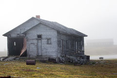 Abandoned old hunting house in tundra of Novaya Zemlya archipelago. Wooden hunting Lodge in open tundra, partially destroyed by hurricane stock photo