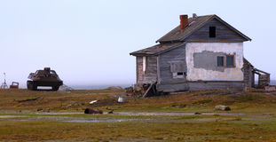 Abandoned old hunting house in tundra of Novaya Zemlya archipelago. Wooden hunting Lodge in open tundra, partially destroyed by hurricane royalty free stock images