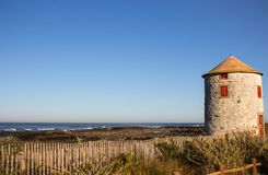 Abandoned old lighthouse with closed red door and windows on Atlantic ocean coast, Portugal. Lighthouse against blue sky. Abandoned old lighthouse with closed royalty free stock photos