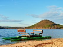 Abandoned old pedal boat caught on sea sandy beach at sunset. Island with forest at horizon. Stock Photography