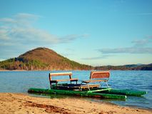 Abandoned old pedal boat caught on sea sandy beach at sunset. Island with forest at horizon. Stock Photos