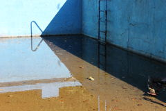 Abandoned old pool. With rusty ladder Stock Images