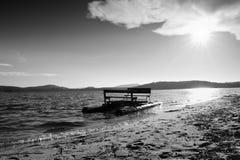 Abandoned old rusty paddle boat stuck on sand of beach. Wavy level, islad on horizon. Autumn weather Royalty Free Stock Image