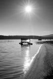 Abandoned old rusty paddle boat stuck on sand of beach. Wavy water level, island on horizon. Royalty Free Stock Photo