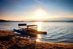 Abandoned old rusty pedal boat stuck on sand of beach. Wavy water level, island on horizon. Autumn sunny at coastline Royalty Free Stock Image