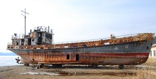 The abandoned old rusty ship. Is placing on the coast of lake Royalty Free Stock Photography