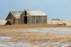 Abandoned old sheds and farm machine in winter Royalty Free Stock Photography