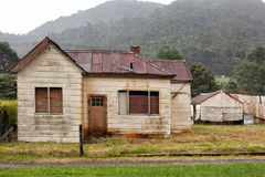 Abandoned old timber home. Old abandoned weatherboard home and shed in Queenstown, Tasmania stock images