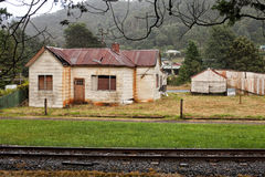 Abandoned old timber home. Old abandoned weatherboard home and shed in Queenstown, Tasmania royalty free stock image