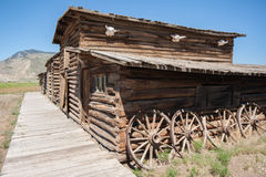 Abandoned Old West Log Building. An abandoned old log building in Cody Wyoming from the American Wild West. Wooden walk antlers and wagon wheels on the side stock photos