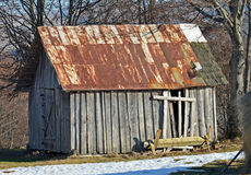 Abandoned old wooden barn with rusted roof Royalty Free Stock Photo