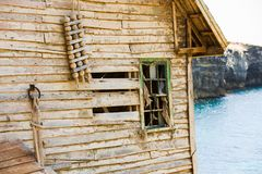 Abandoned old wooden board house ruin next to sea shore Royalty Free Stock Images