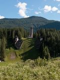 Olympic Ski Jumping Trampoline in Summer Time. Abandoned Olympic Ski Jumping Trampoline among Mountains Scenery in Summer Time Stock Photo
