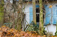 Abandoned one-story house with leaning fence in thickets on former street in Chernobyl Chernobyl exclusion zone, Ukraine stock photography