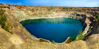 Open pit mine full of water. A panorama of an abandoned open pit mine full of water Royalty Free Stock Photos