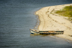 Abandoned oyster boat on beach Stock Photos