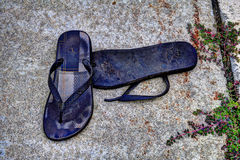 Abandoned. A pair of flip flops left lying on sidewalk royalty free stock photo