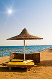 Abandoned  parasol and yellow towel on the resort. Stock Photography