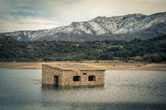 Abandoned and partially submerged stone building in lake in Cors Stock Image