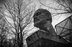 Abandoned pedestal with a giant head of Lenin on a background of dead trees (black and white).  Stock Image