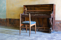 Abandoned piano and broken chair Royalty Free Stock Photos