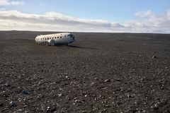 Plane wreckage in Iceland. Abandoned plane wreckage on the Solheimasandur beach on the background of the blue sky with few clouds in Iceland. Sun shines on it Royalty Free Stock Photo