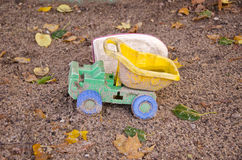 Abandoned plastic truck toy in autumn sand box Royalty Free Stock Photo