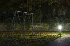 Abandoned playground 1. An empty playground with metal swings at night with fog and creepy atmosphere royalty free stock image