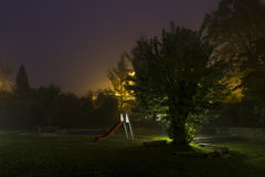 Abandoned playground 3. An empty playground with a red slide at night with fog and creepy atmosphere stock images