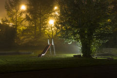 Abandoned playground 2. An empty playground with a red slide at night with fog and creepy atmosphere royalty free stock photos