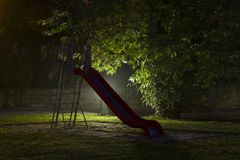 Abandoned playground 4. An empty playground with a red slide at night with fog and creepy atmosphere stock photography