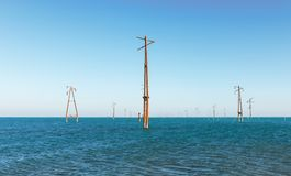 Abandoned power lines. In sea Royalty Free Stock Images