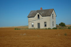 Abandoned Prairie Farm Home 2. Abandoned farm house on the lonely prairie with clear blue sky and surrounded by mature grain crop Royalty Free Stock Photography