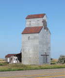 Abandoned prairie grain elevator. Old abandoned American prairie grain elevator next to an old highway, against a blue sky Royalty Free Stock Photo