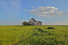 Abandoned Prairie Home. An old abandoned house resides in the long prairie grass, surrounded by a fence Stock Photo