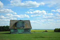 Abandoned Prairie Homestead. Old Farm House against a canola field and blue sky Royalty Free Stock Photography