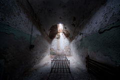 Abandoned prison cell with a old bed frame. Light shining on a creepy old cell in Eastern State Penitentiary Stock Photo