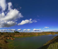 Abandoned quarry, blue sky and white clouds Stock Photos