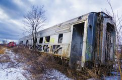 Abandoned railroad car in field with snow. Abandoned silver railroad car in field with snow bare trees and brush and locomotive in background royalty free stock photography