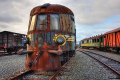 Abandoned railroad engine. And carriages standing on rusty rails (an HDR image royalty free stock photo