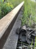 Abandoned railroad track close up. Close up on abandoned railroad track with blurry background, rusty bolts green grass growing over it royalty free stock photos
