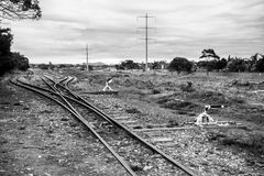 Abandoned railway - paths that merge. An old railway line, separating into different routes in the distance. Power-lines balance the horizon, along with a few royalty free stock images
