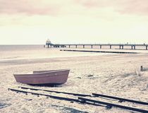 Abandoned red paddle boat on sandy beach of sea.  Smooth water level Royalty Free Stock Photo