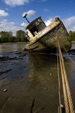 Abandoned Riverboat. An abandoned, vandalized, rotting fishing boat on the muddy banks of a low river stock image